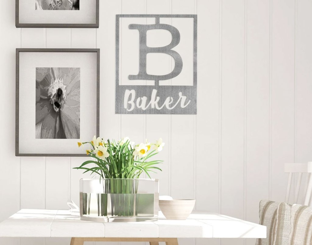 steel monogrammed plaque on wall with large B that says Baker next to other framed photos