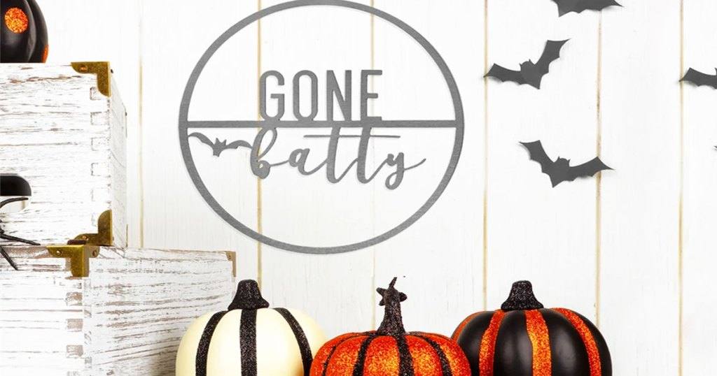 round metal sign that says gone batty on wall with bat decals and sparkly pumpkins