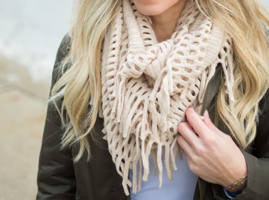 woman wearing an army green jacket and cream colored fringe scarf