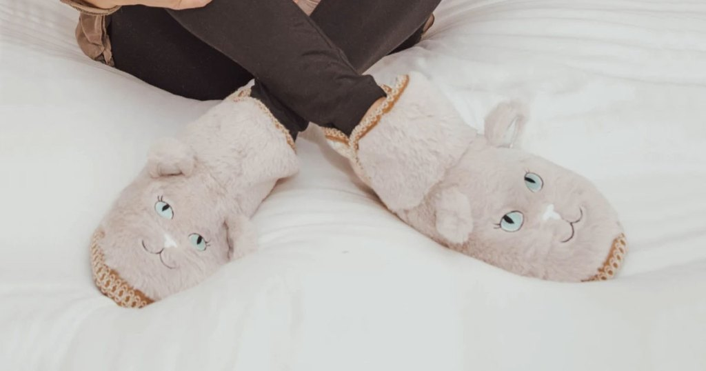 woman sitting on bed wearing a pair of cat shaped fuzzy slippers
