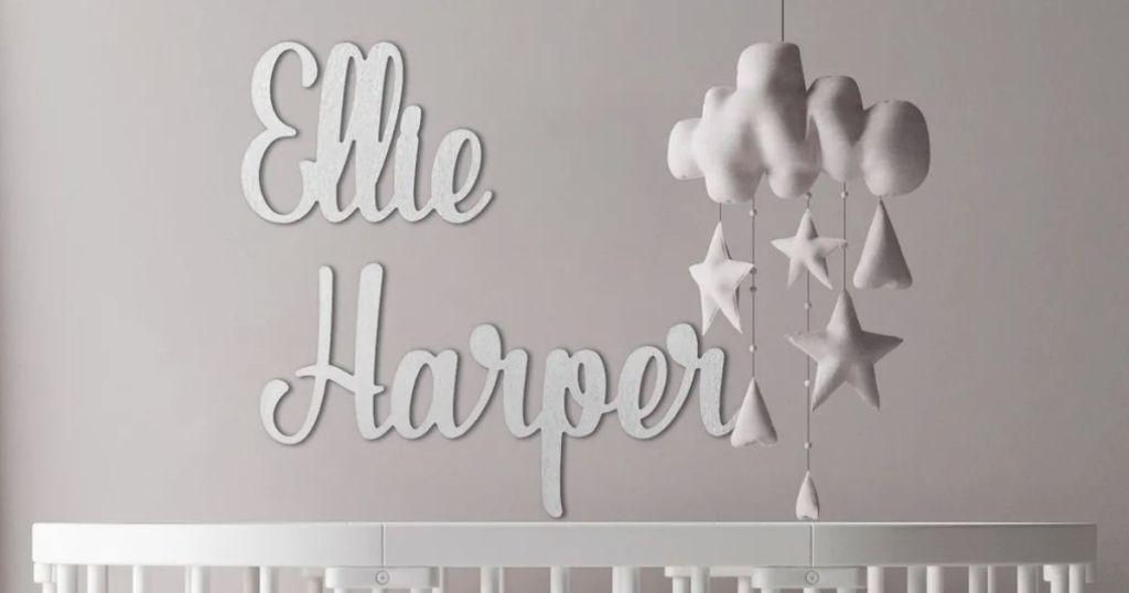 name sign hanging on nursery wall above crib