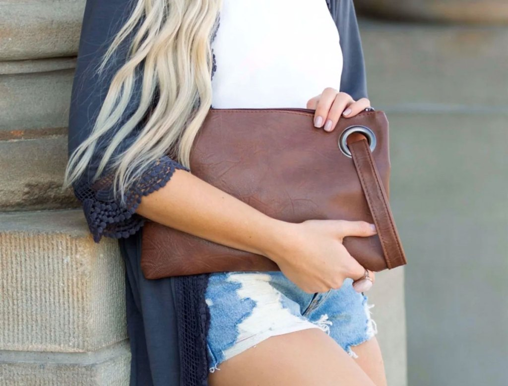 woman in jean shorts and blue top holding a brown leather oversized clutch
