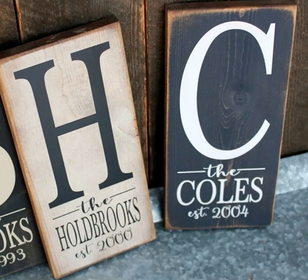 two wooden personalized signs with last names and years family was started