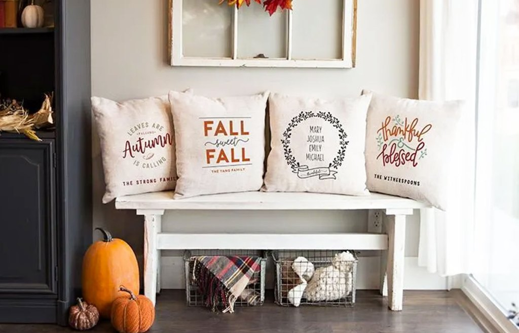 four fall themed personalized throw pillows on white wooden entryway bench