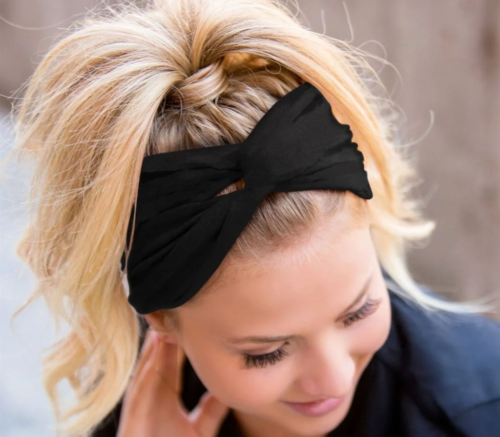 woman with blonde hair in pony tail and black twist headband