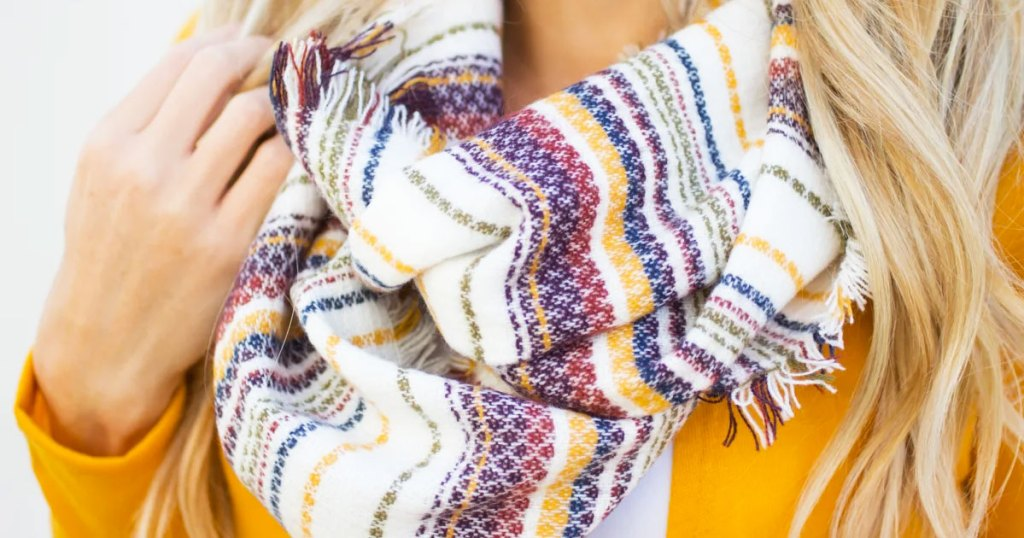 blonde woman wearing yellow sweater and multi color striped infinity scarf