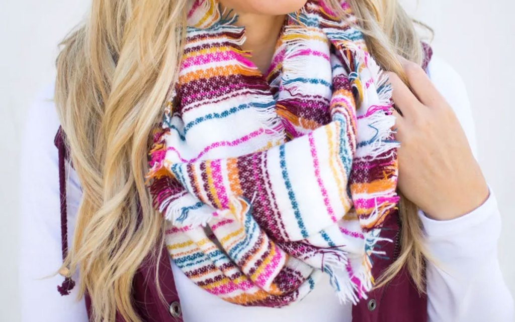 blonde woman wearing a pink and red striped infinity scarf