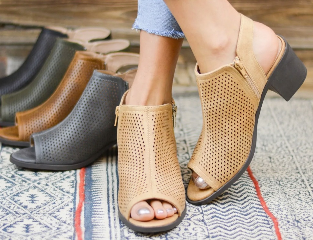 woman wearing a pair of tan peep-toe booties with other colors of booties behind her