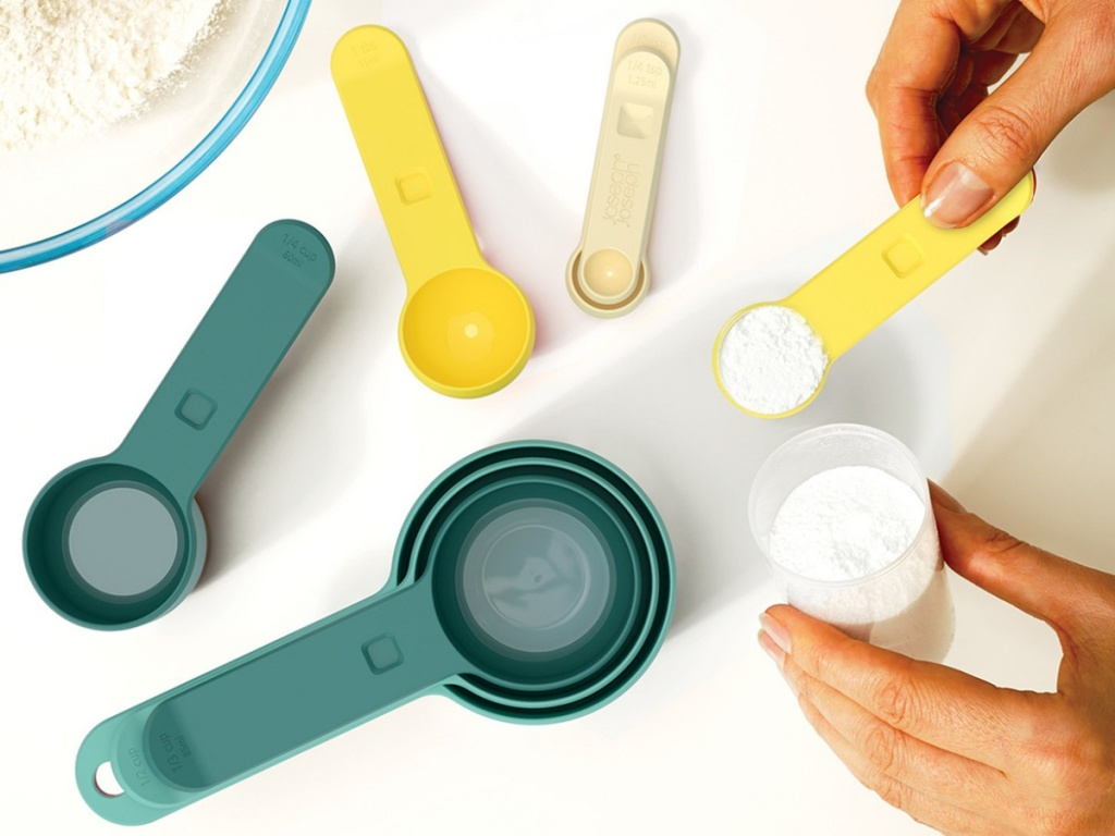hands using yellow measuring spoon, green and yellow measuring cups, bowl of flour