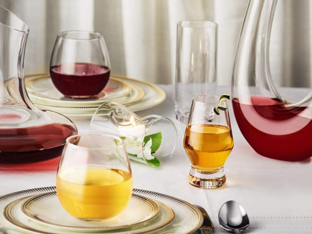 joyjolt stemless wine glasses sitting on dinner plates next to a wine decanter