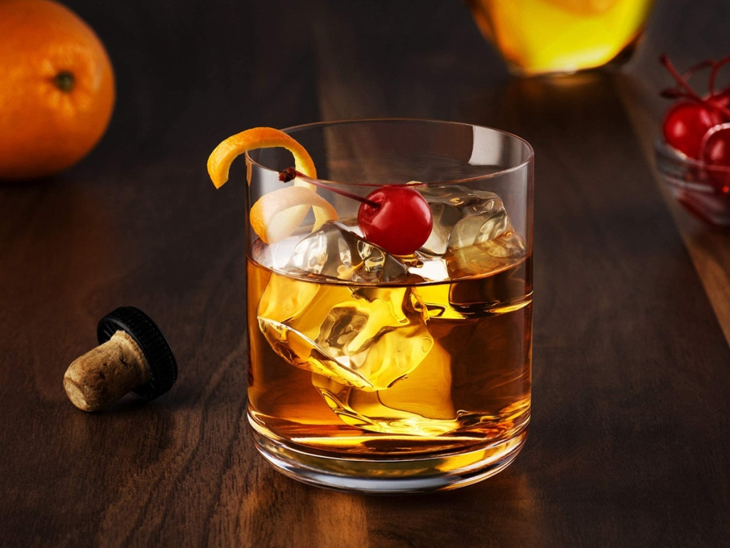 whiskey rocks glass filled with ice, whiskey and a cherry on top on a dark brown counter next to a orange and other fruit