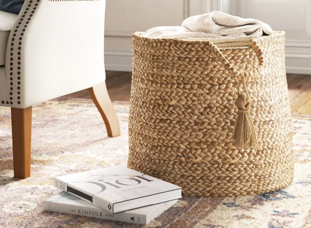 tall woven basket on floor next to chair and stack of books