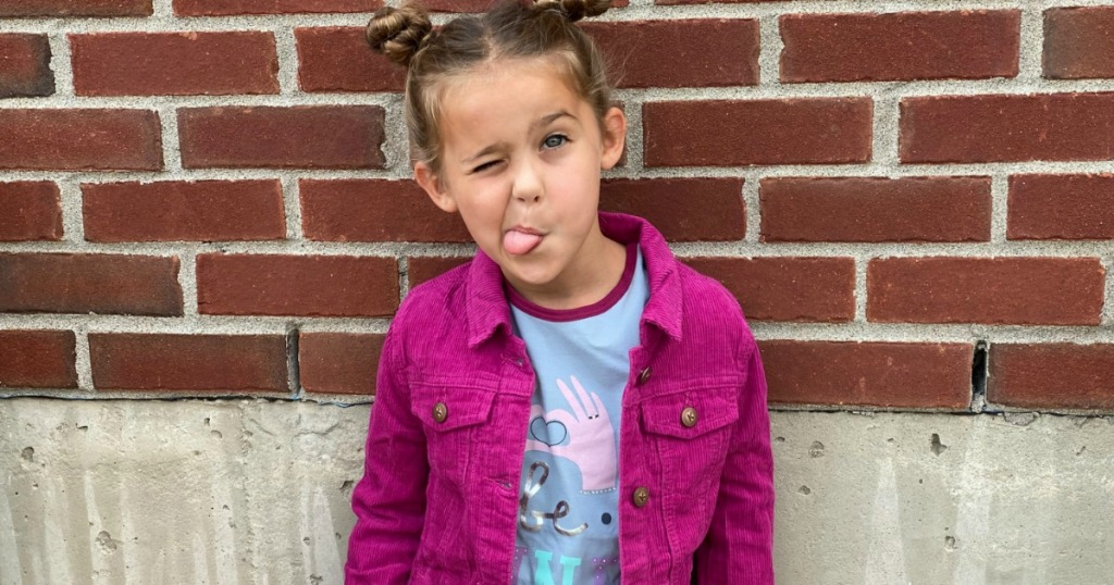 young girl wearing a pink denim jacket and making a silly face in front of a brick wall