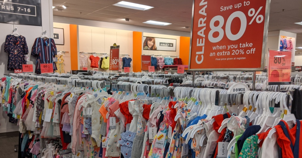 kids clothes hanging in store and clearance sign