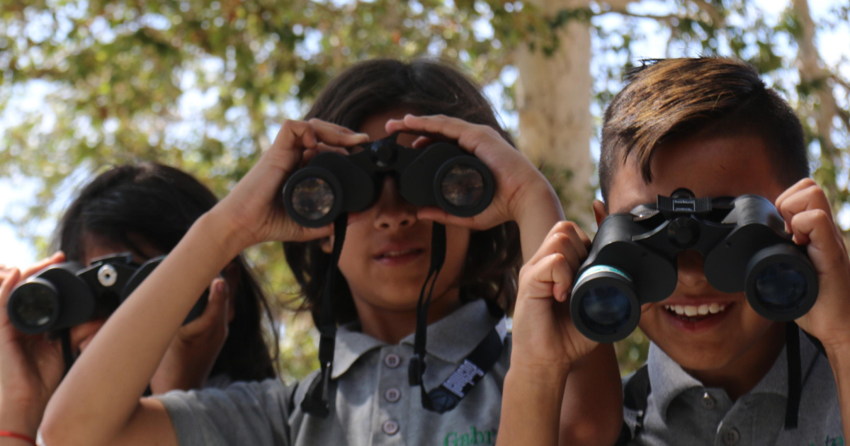 kids outdoors looking thru binoculars