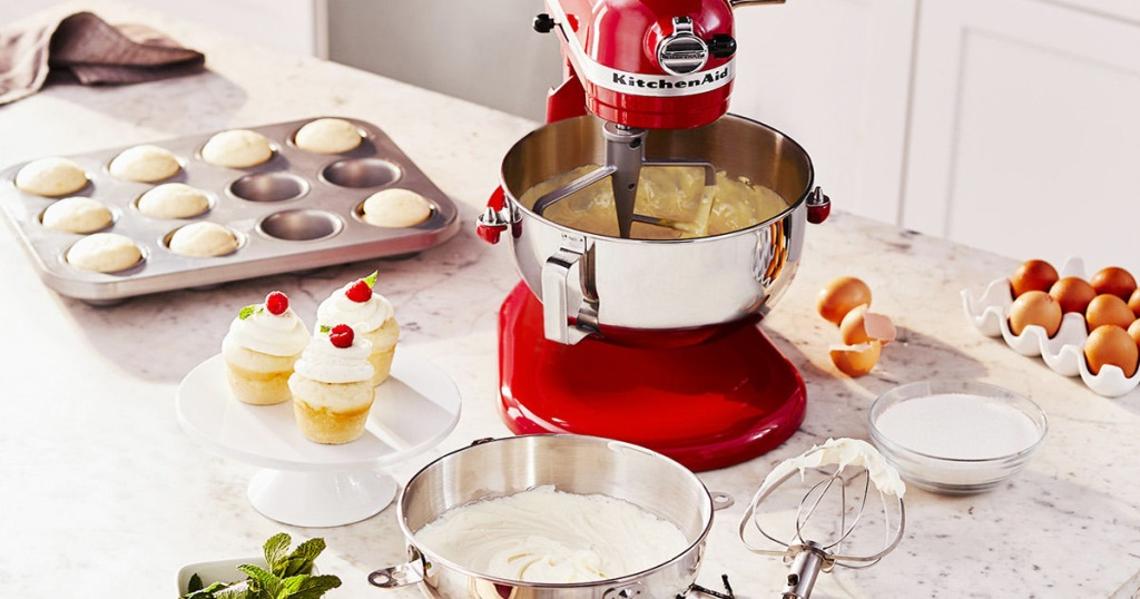 red KitchenAid mixer on counter with cupcakes and baking ingredients around it