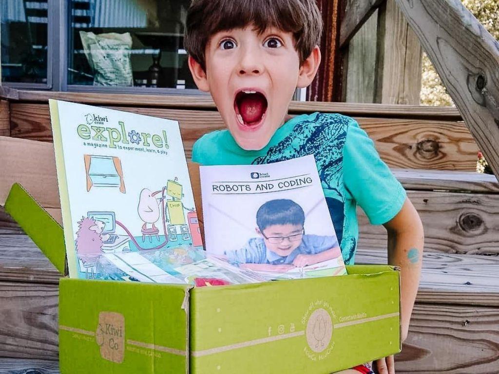 kid holding a kiwico box