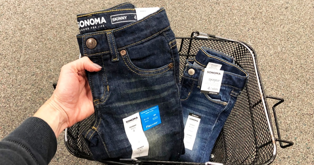 woman holding up pair of sonoma girls jeans from black shopping basket on floor
