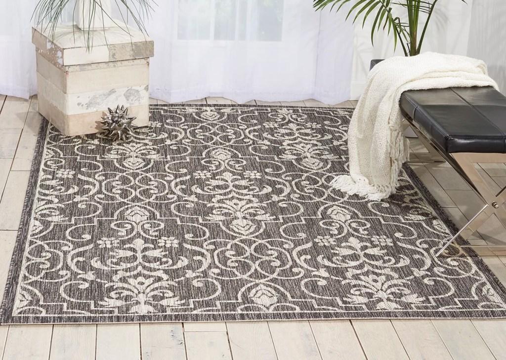 grey and cream scroll area rug on hardwood floor