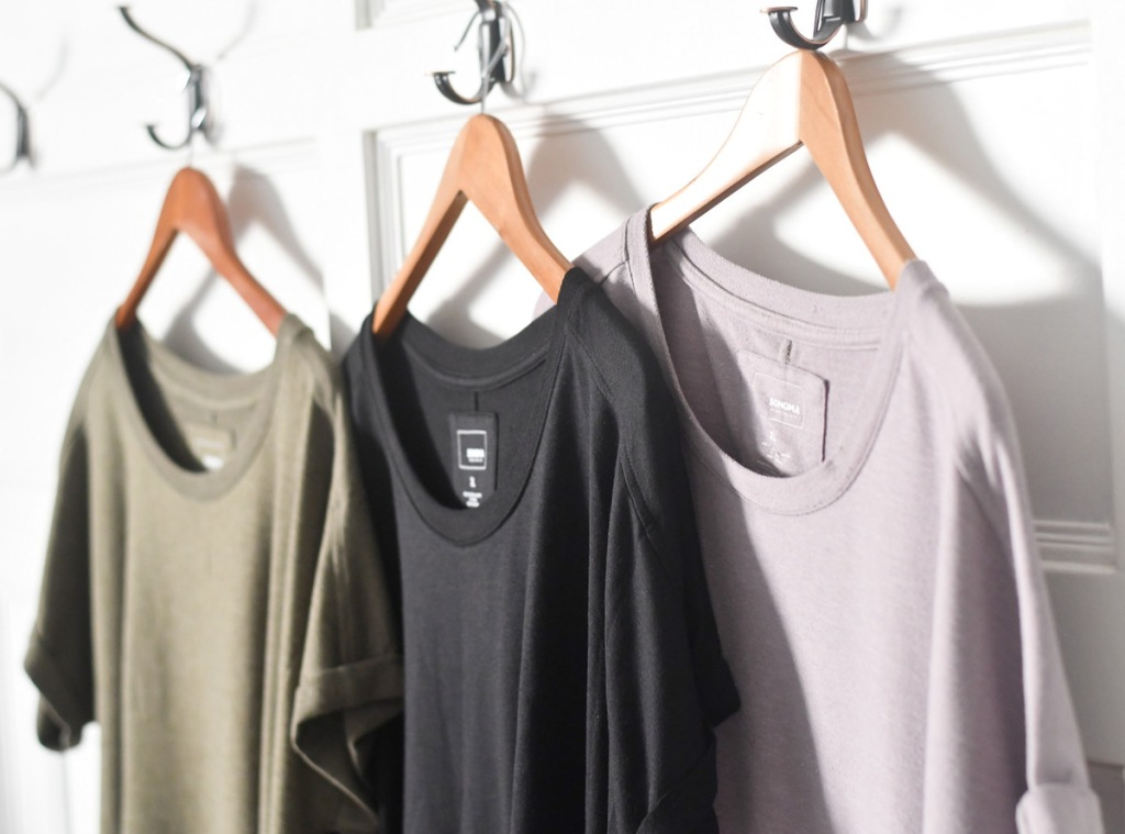 olive green, black, and mauve colored tunic tops hanging on wooden hangers