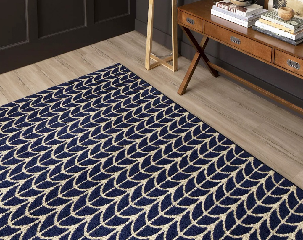 navy blue and tan chevron print area rug on hardwood floor