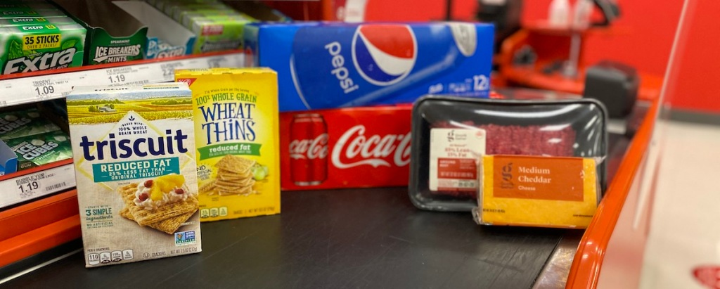 triscuits, wheat thins, pepsi, coke, ground beef, and cheddar cheese on checkout lane