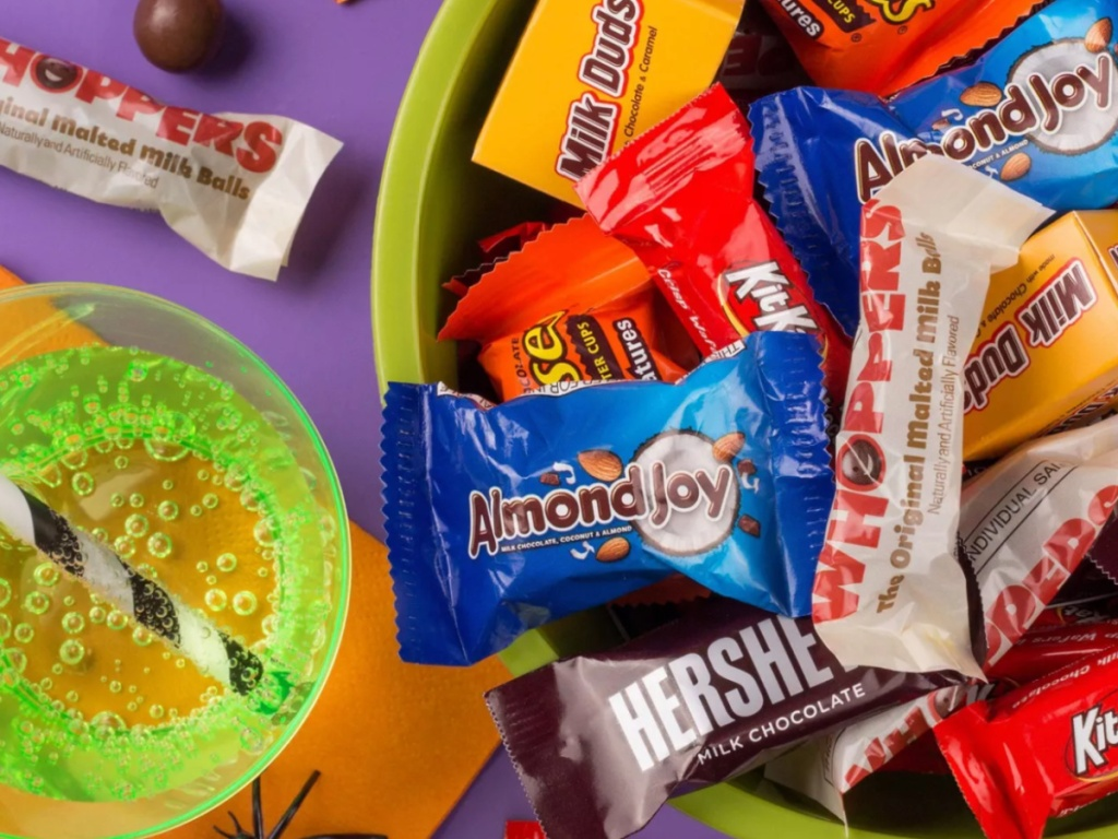bowl os Halloween candy next to a green soda and black and white straw