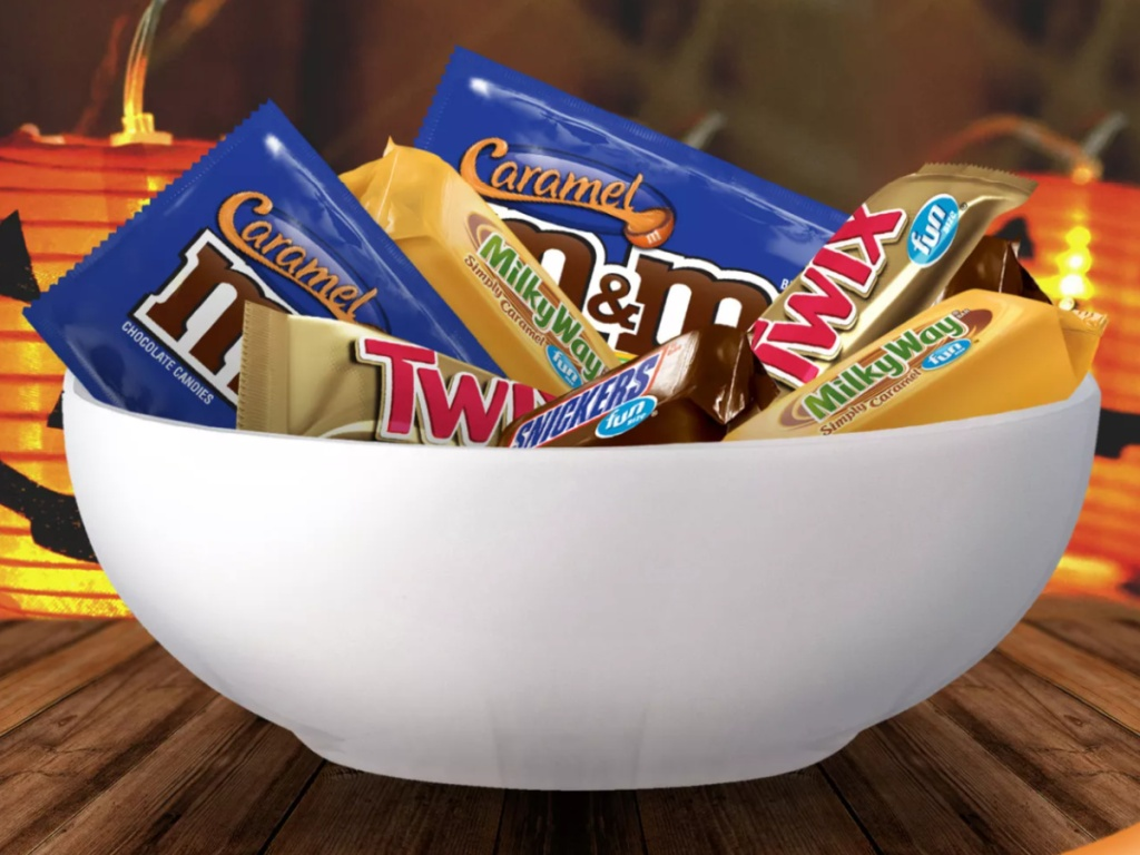 Large bowl of Halloween Candy in front of several lighted jack-o-lanterns