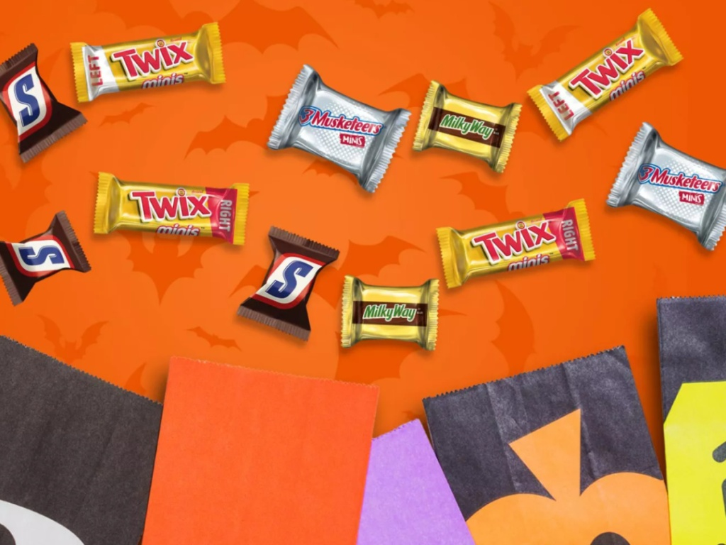 Small Mars individual Halloween candies next to Halloween p[aper bags