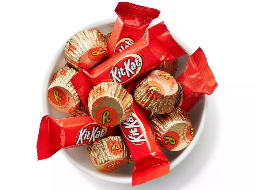 White dish filled with reese's peanut butter cups and kit bar candy bars