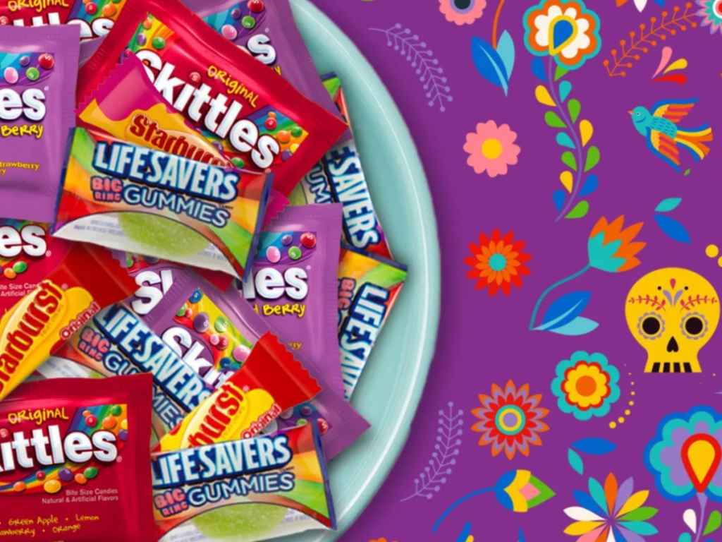 Large blue dish filled with skittles halloween candies