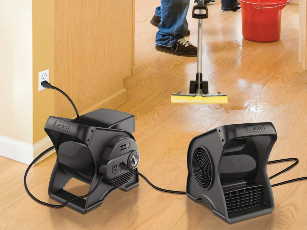 2 lasko black pivoting fans sitting on a floor with someone mopping behind them