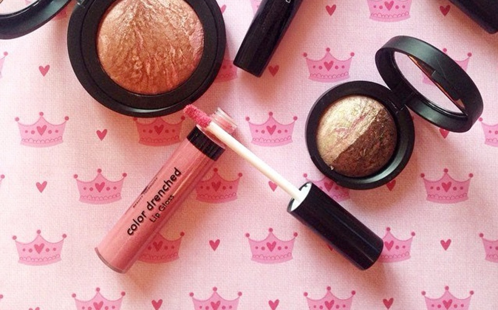 travel size Laura Geller lip gloss in pink shade near bronzers on a pink background with crowns