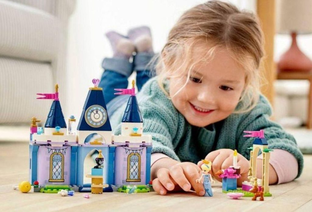 little girl playing with lego castle