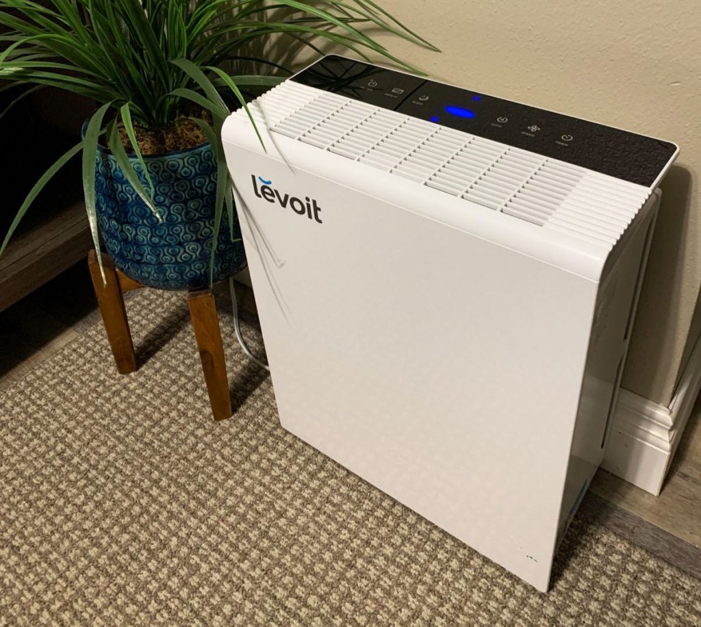 white rectangular air purifier on floor near potted indoor plant