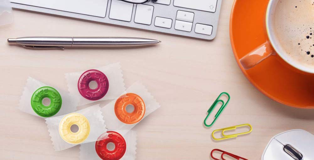 LIfe savers candy on a desk with pen and paper clips
