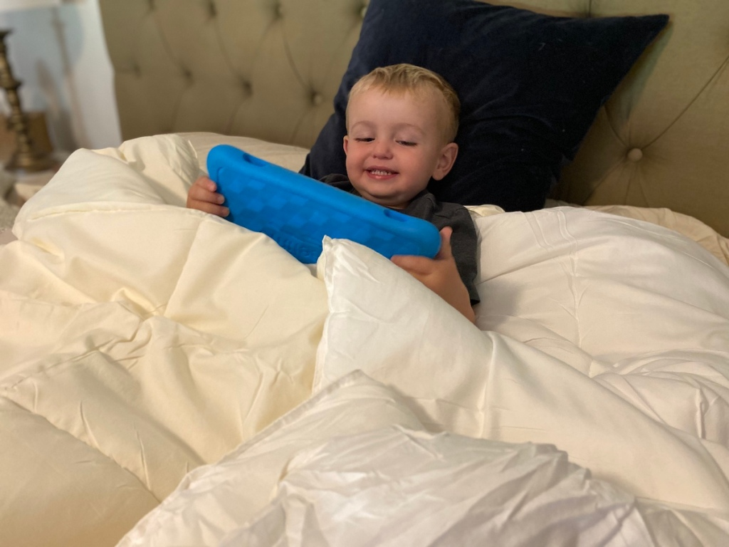 boy looking at a tablet in bed