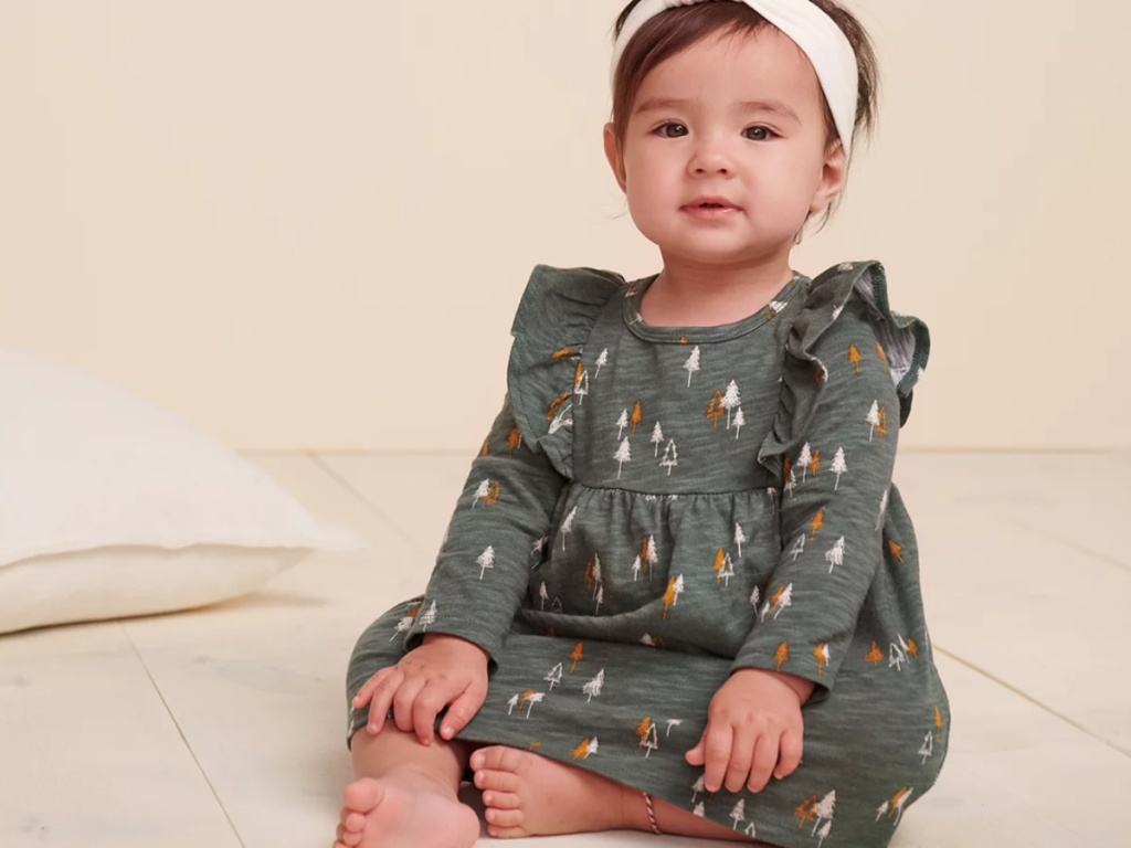 baby girl sitting on the floor wearing a cute fall dress and matching headband