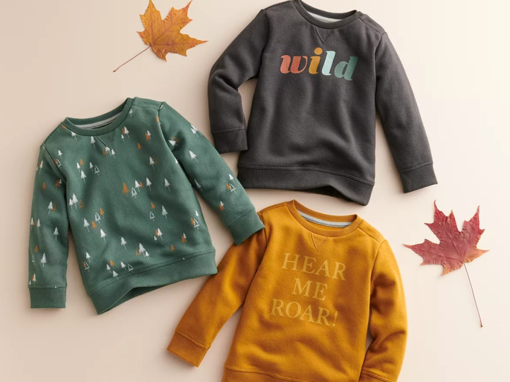 Cute fall sweatshirts for kids next to leaves