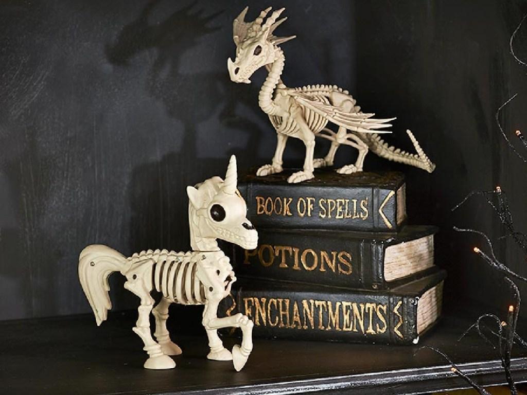skeleton animals sitting on a black shelf next to halloween books