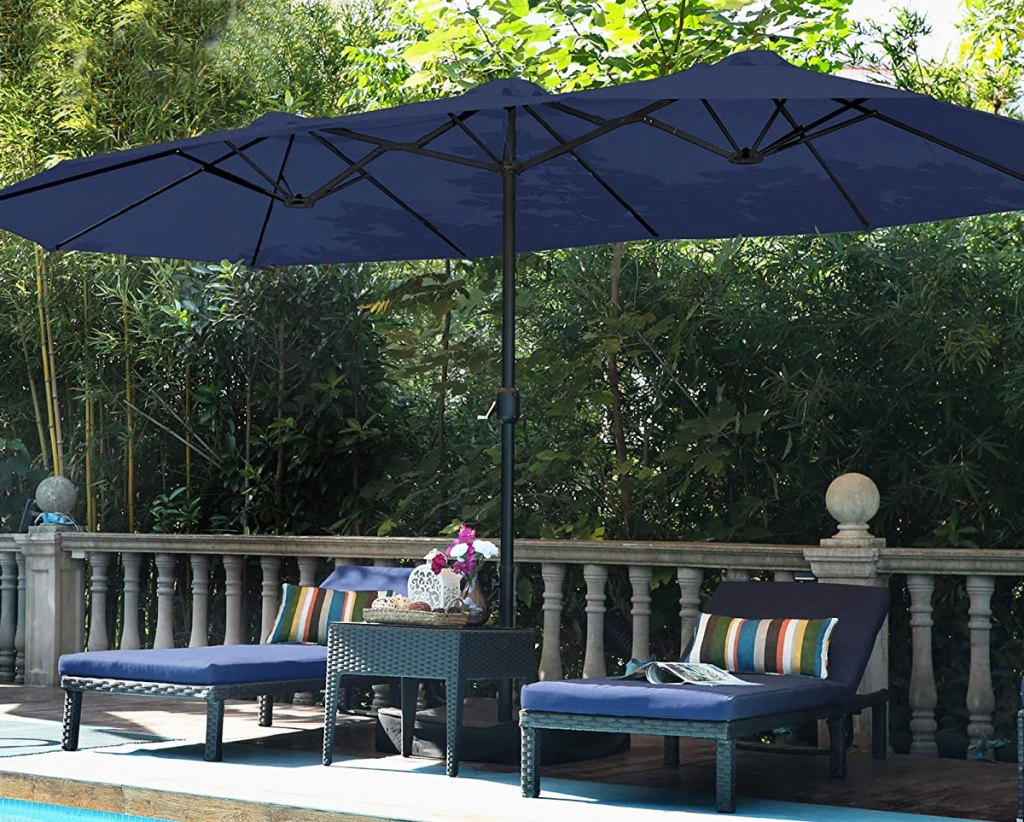 navy blue extra-large patio umbrella over two navy blue lounge chairs by pool