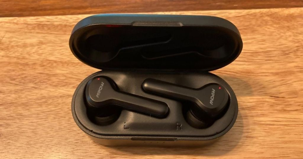 wireless earbuds in case on wood surface
