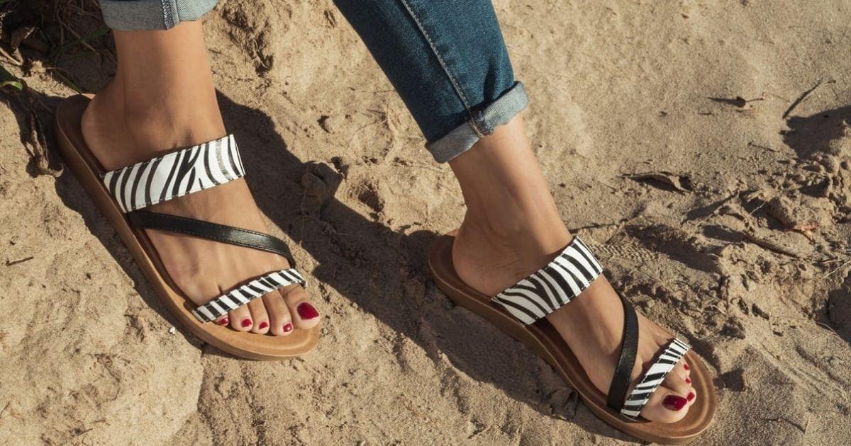 woman's feet wearing zebra sandals on sand