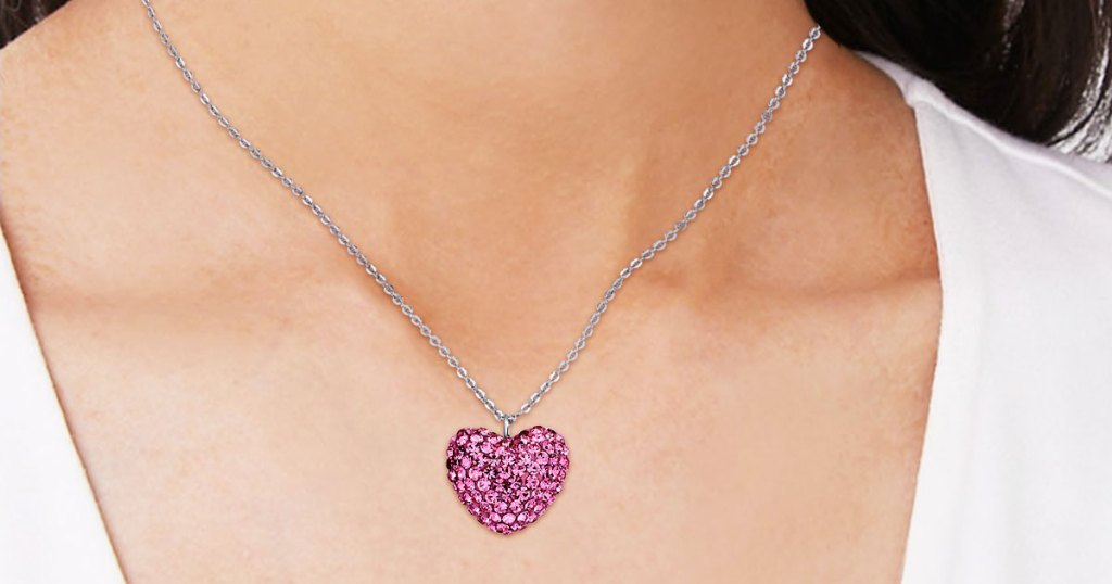 woman wearing a white t-shirt and a pink puffy heart shaped gemstone necklace