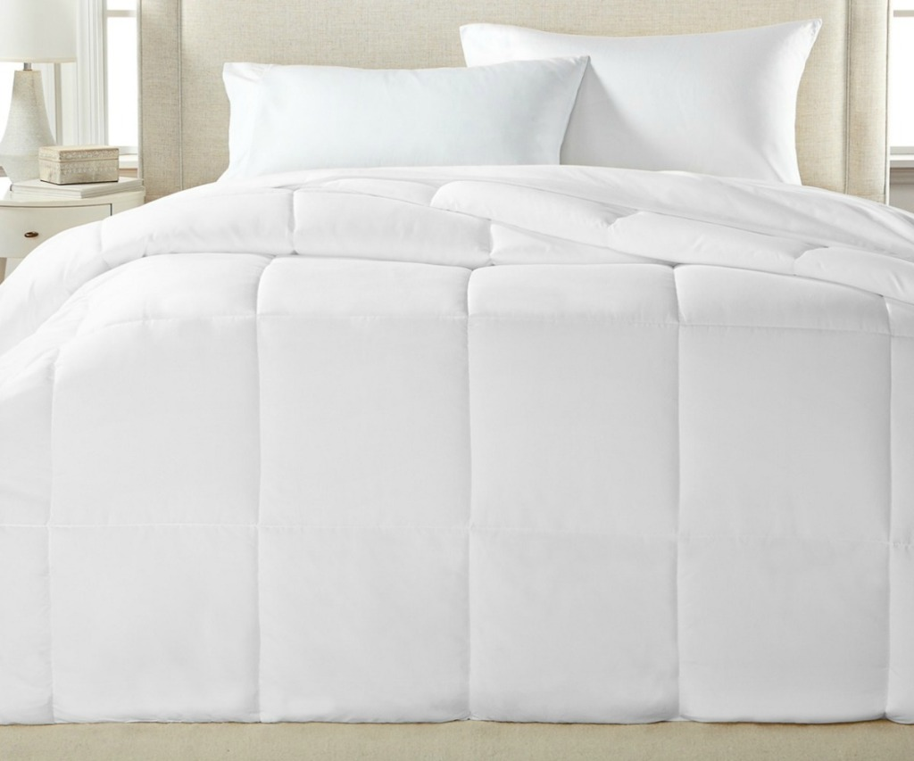 Large white comforter on a bed with two standard sized pillows