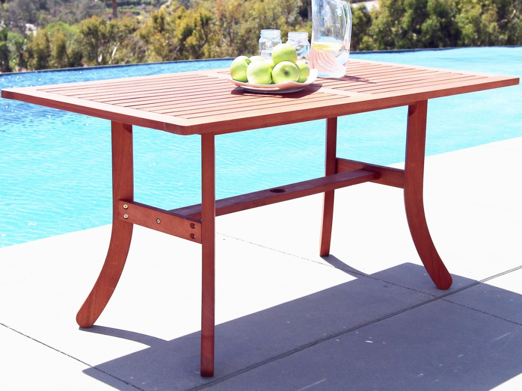 wood outdoor table in front of pool