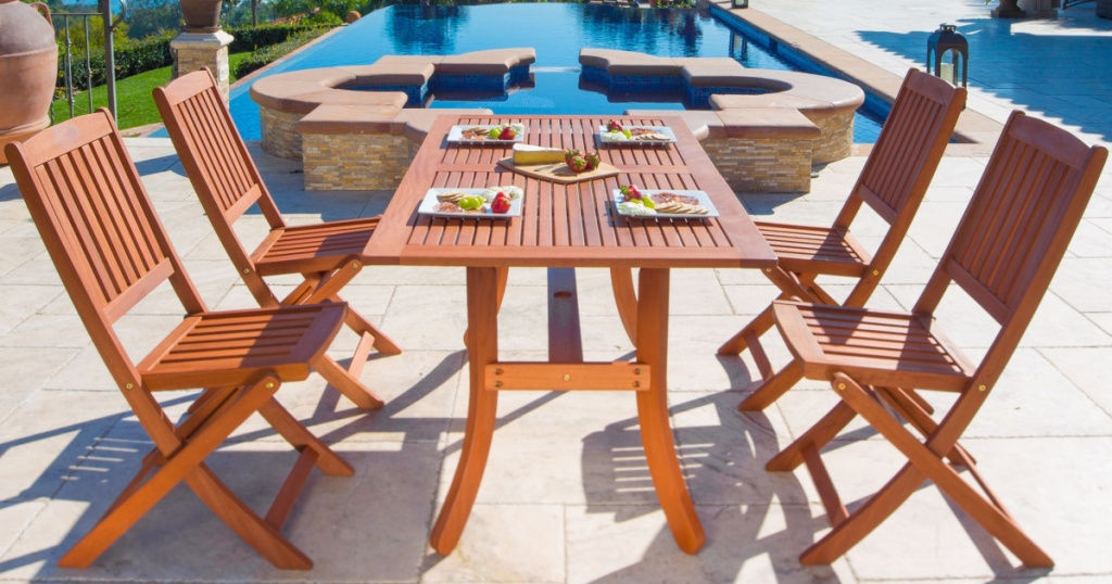 wood outdoor dining table and chairs in front of pool