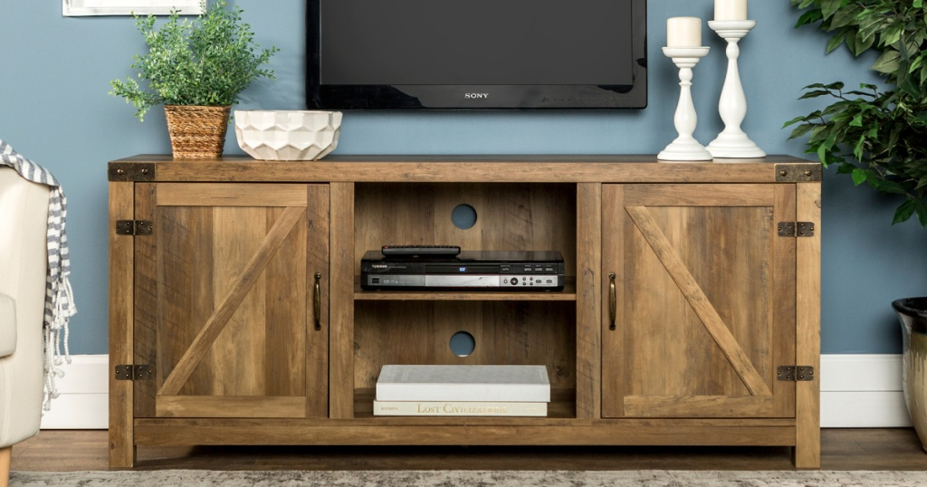 wood farmhouse style tv stand, tv mounted on wall, plants, and more in home