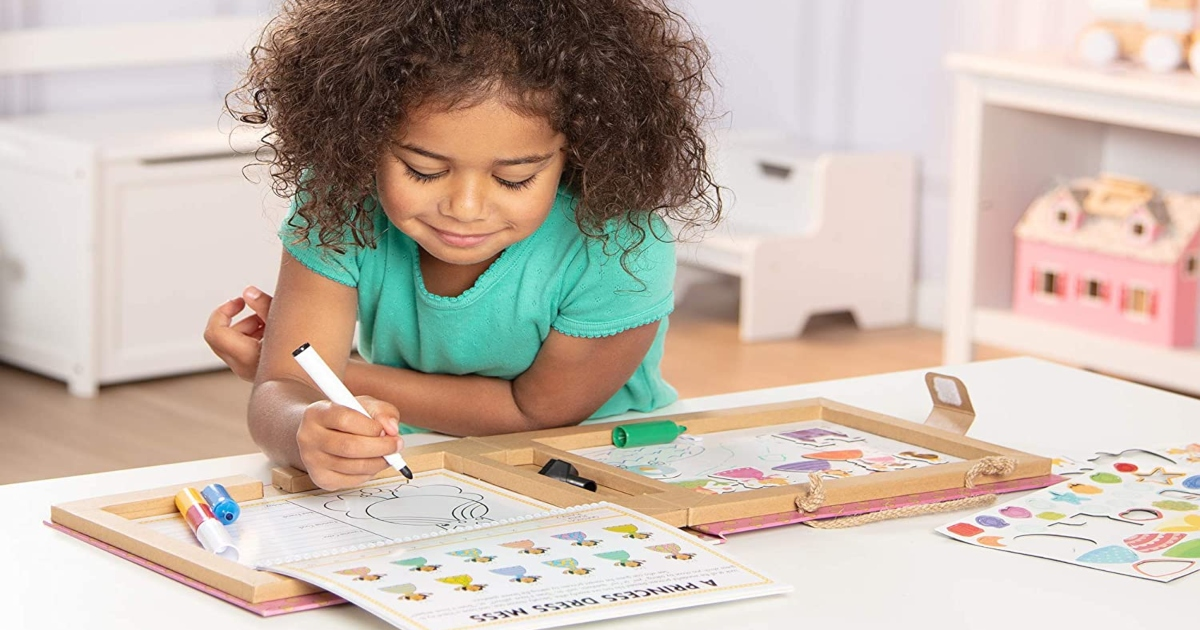a girl sitting at a table with the Melissa & Doug activity kit open. she is drawing