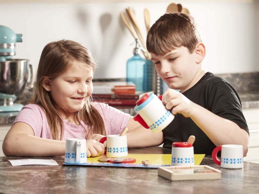 two children playing with a melissa & doug tea playset